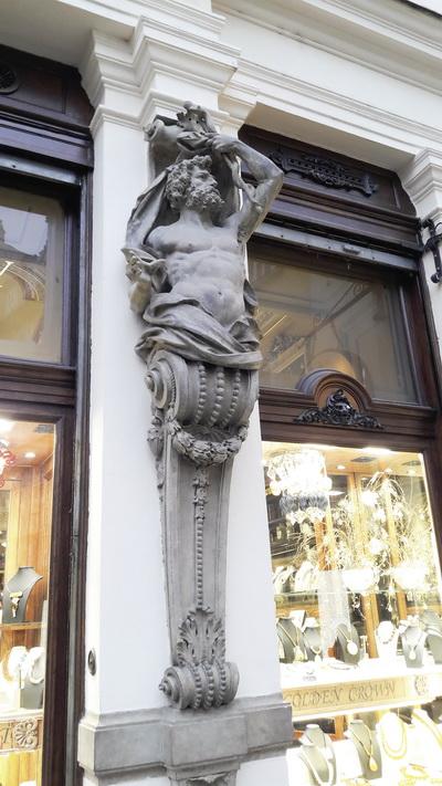 Вхід в аптеку прикрашають фігури Асклепія (праворуч) з типовими символами фармації та бога торгівлі Меркурія (ліворуч), якого середньовічні аптекарі почитали не менше